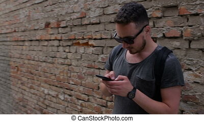 Guy uses a smartphone near a brick wall