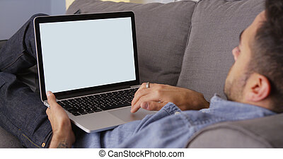 Guy using laptop on couch