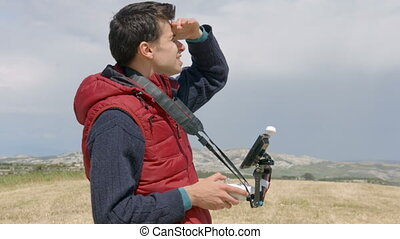 """""""Guy using remote control to film aerial video with drone mounted camera, robot"""""""