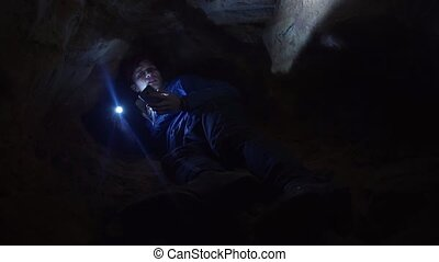 Guy using smartphone laying on ground into closely hole in cave with flashlight