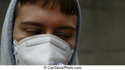 guy walking in an hostile city with a facial mask in difficult times like the COVID19 ones