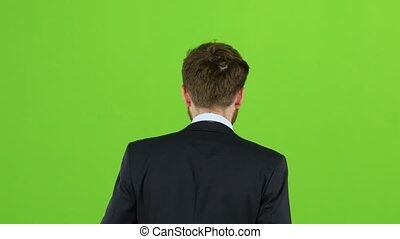Guy walks down the street, puts his hand in his pocket and waves. Green screen. Back view