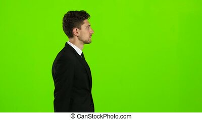 Guy walks down the street, puts his hand in his pocket and waves. Green screen. Side view