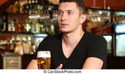 Guy watching sports at bar and rejoicing