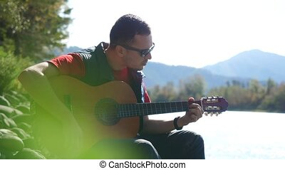 Guy wearing sunglasses plays on a guitar singing song sitting by mountain river on sunny day. 3840x2160