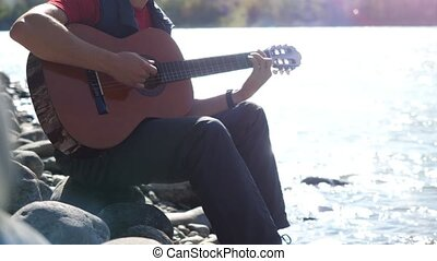 Guy wearing sunglasses plays on a guitar sitting by mountain...