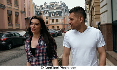 Guy wearing white t-shirt with a girl in a checkered shirt walking down the street holding hands and looking at each other