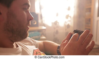 Guy with a beard using his smartphone side view. Video full...