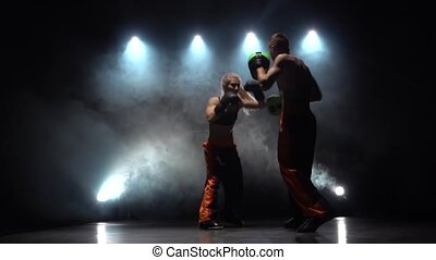 Guy with a girl boxing gloves beating in the ring in the dark, they are preparing for a kickboxing competition. Silhouette. Light from behind. Smoke background. Slow motion
