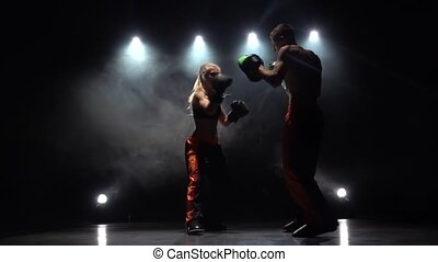 Guy with a girl boxing gloves beating in the ring . Light from behind. Smoke background. Slow motion