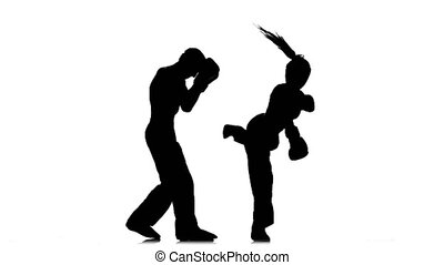 Guy with a girl in helmets and boxing gloves beating in the...