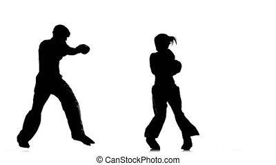 Guy with a girl in helmets and kickboxing gloves beating in the ring . Silhouette. White background