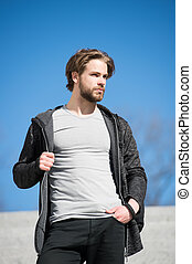 Guy with beard and haircut in grey tshirt standing