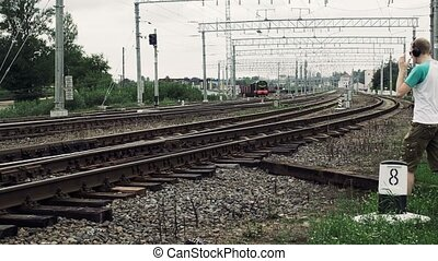 Guy with headphones crosses a railway or railroad in the...