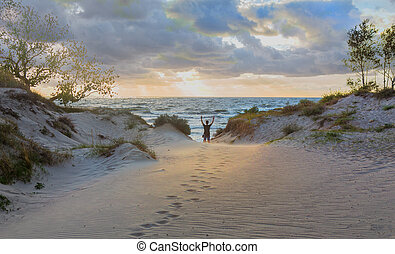 guy with his hands up on the shore of a stormy sea