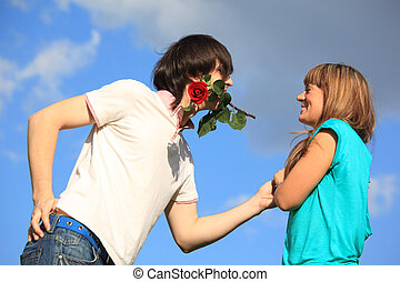 guy with rose in mouth and girl against sky