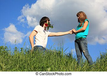 guy with rose in mouth and girl in grass