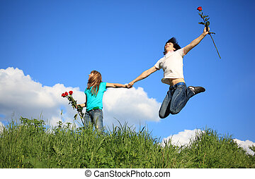 guy with rose jumps holding girl with roses by hand