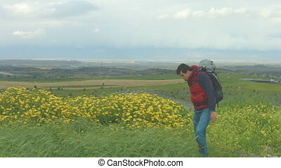 """Guy with rucksack walking in beautiful field, tourist..."
