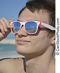 Guy with sunglasses that reflect the sea and the Burj Al Arab, Dubai. Young man at the beach smiling and holding sunglasses, close-up