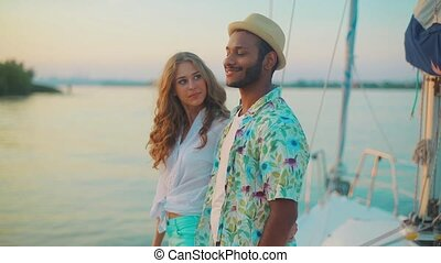 Guy with the girl meets a sunset on the yacht.