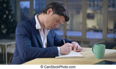 Guy writing notes sitting at the desk