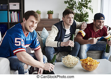 Guys celebrating football match in house