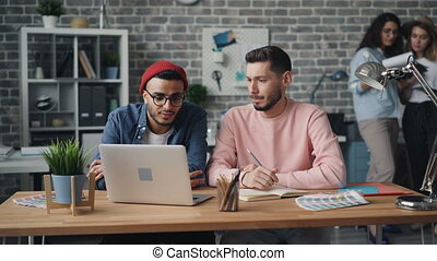 Guys coworkers speaking looking at laptop screen working in office together