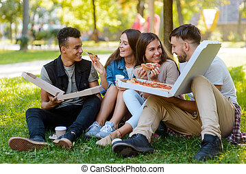 Guys dining at the park. Two delicious pizzas for four friends