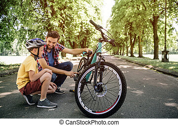 Guys have a short break during theit trip on bicycles. They are sitting at the border of road. Man is holding bicycle and looking at his son. Child is looking straight forward.