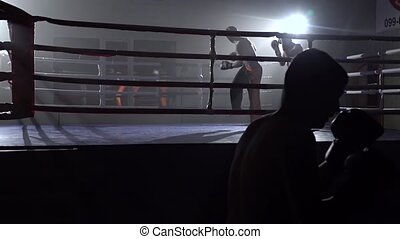 Guys in gloves beats a pear, in the background in the ring...