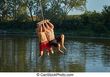 Guys jumping in a river