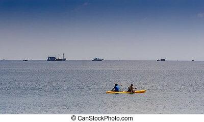 Guys Paddle Kayak along Azure Sea against Skyline