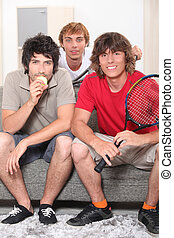 Guys sitting on sofa with tennis rackets