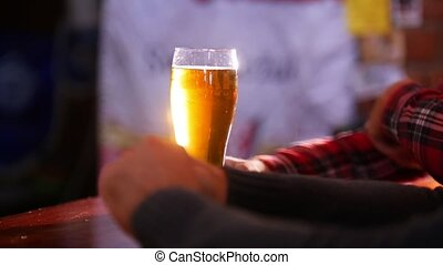 Guys talking in the pub, guy takes a sip of beer and puts it...