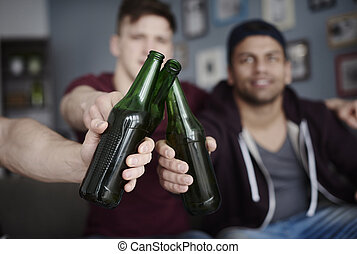 Guys toasting with beer bottles