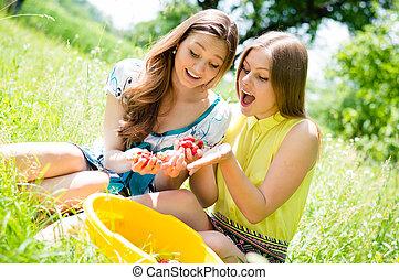 gyönyörű, nyár, étkezési, fiatal, két, gyönyörködtet, földieprek, zöld háttér, szabadban, lány friends, nők