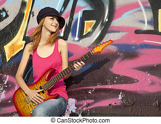 gyönyörű, red-haired, leány, noha, gitár, és, falfirkálás, fal, -ban, háttér.