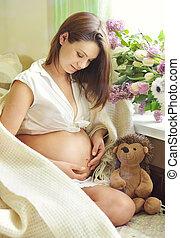 gyönyörű, terhes nő, ül dívány, közel, ablak, és, cirógató,...