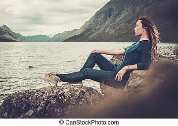 gyönyörű woman, feltevő, képben látható, a, tengerpart, közül, egy, vad, tó, noha, hegyek, képben látható, a, háttér.