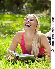 gyönyörű woman, könyv, felolvasás, fű, fekvő, nevető