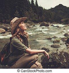 gyönyörű woman, kiránduló, ülés, képben látható, a, megkövez, közel, vad, hegy, river.