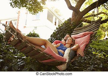 gyengéd, young párosít, fekvő, képben látható, kert, függőágy