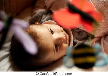 gyermekek játék, otthon, boldog, csinos, kicsi lány, mosolygós, és, játék apró, és, bábu, ágyban