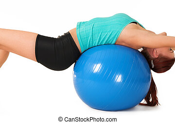 A woman in gym clothes, laying on her back on a Pilates ball