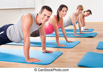 Gym class doing press ups - Group of diverse healthy people...