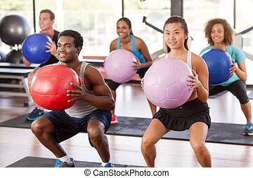 Gym class doing squats - Multi-ethnic gym class doing squats...