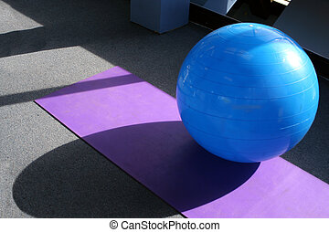 gym equipment - yoga ball and mat at the gym