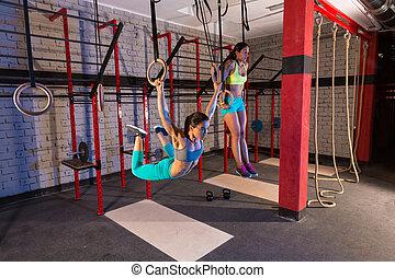 Gym girls muscle ups rings swinging workout at gym