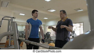 Gym instructor giving consultation to a man - In the gym....